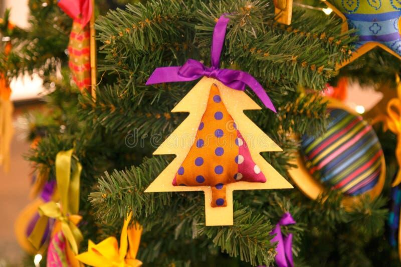Печенье и деревянные игрушки в форме рождественской елки и сердца и розовая птица ткани висят на ветви  стоковые фотографии rf