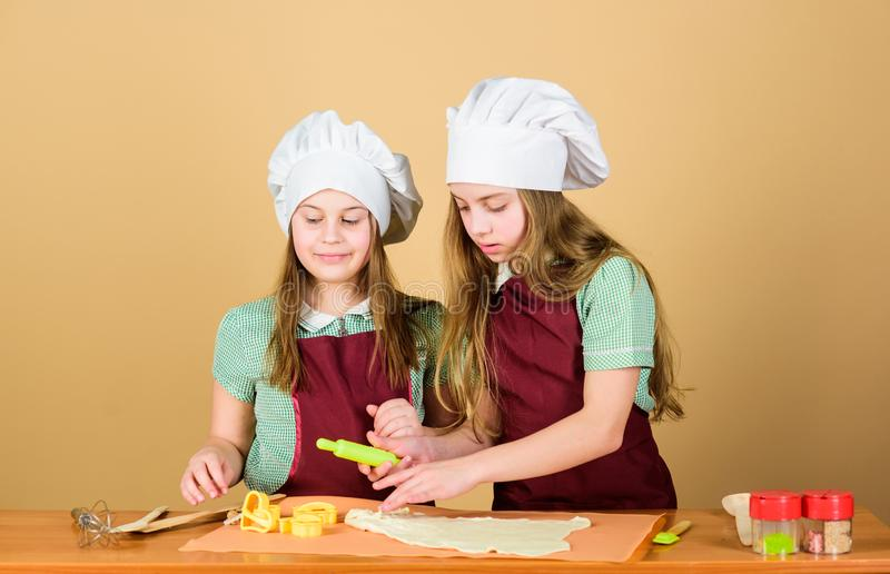 Печенье печется Маленькие дети свертывая тесто для домашней испеченной еды Небольшие девушки подготавливая испеченные крены в кух стоковые фотографии rf