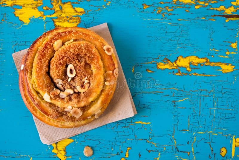 Печенье циннамона и гайки свертывает поверх салфетки на слезать и треснуло голубую и желтую покрашенную древесину сверху Космос д стоковое фото