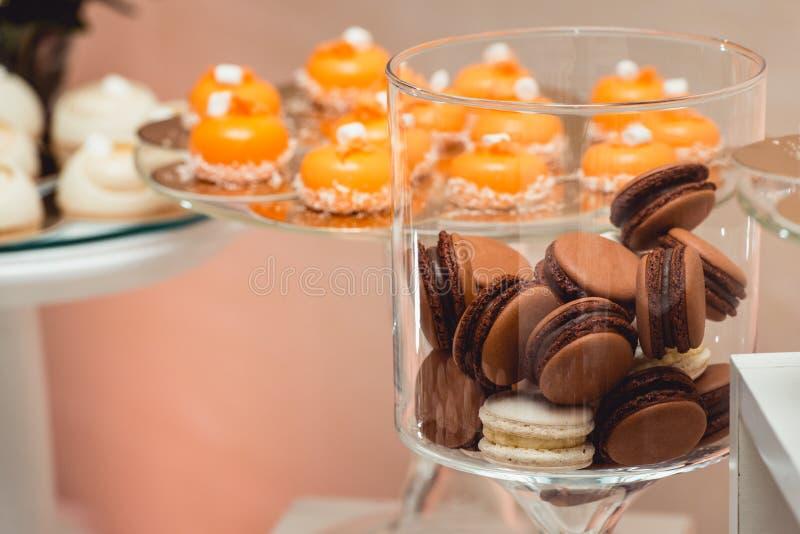 Печенье macaroon красочного пастельного бежевого коричневого ванильного шоколада кофе французское в стеклянном опарнике стоковое фото rf