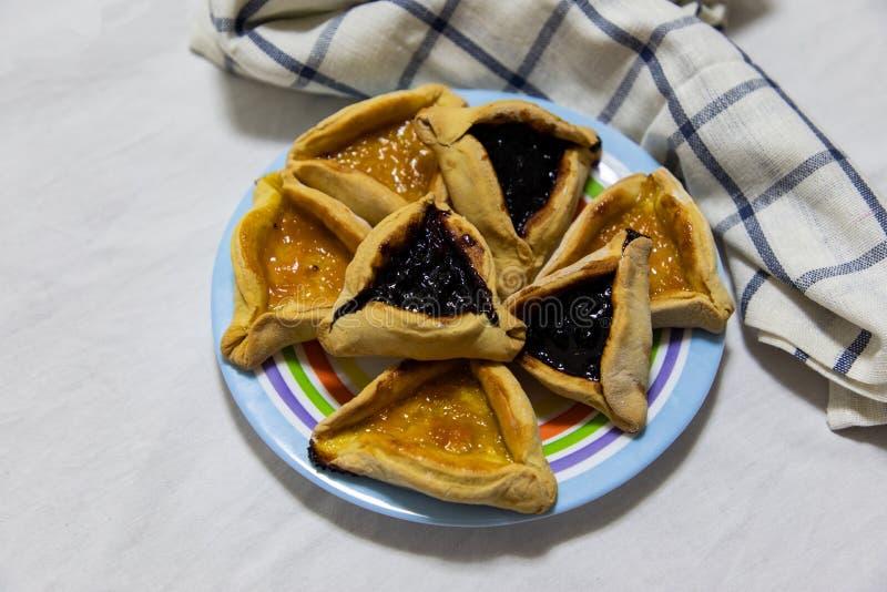 Печенья варенья голубики и абрикоса Hamantash Purim на покрашенной плите с ветошью шотландки голубой и белой предпосылкой листа стоковое изображение