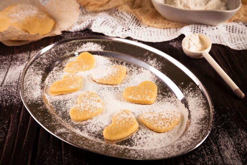 Печенья в металлической пластине сердца формы с мукой на деревянном bac стоковая фотография