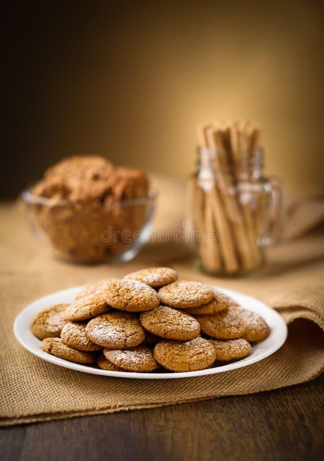 Печенья имбиря меда на переднем плане Печенья изюминки овсяной каши и пируэт свернули вафли на заднем плане Мешковина на деревянн стоковое изображение rf