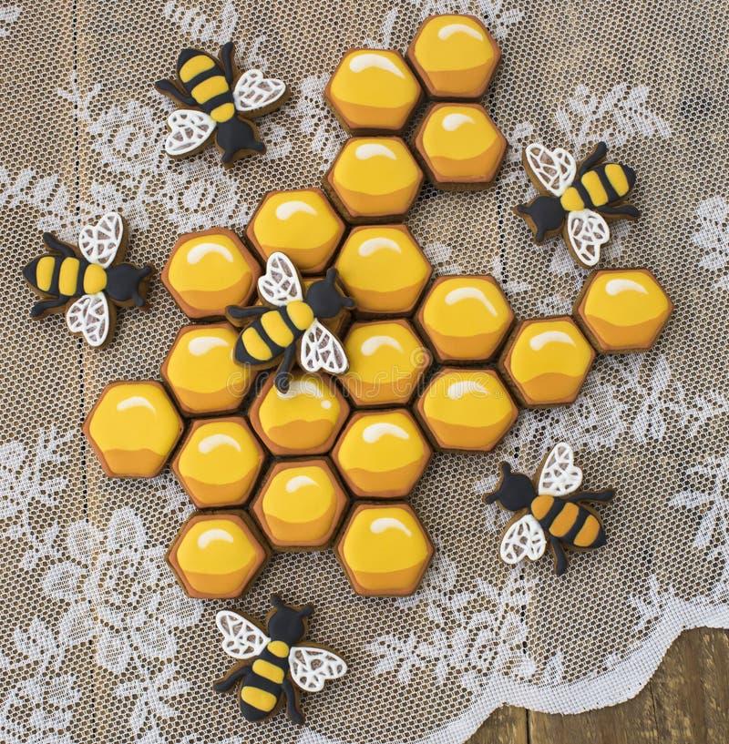 Печенья и пчелы сота на деревянном столе стоковая фотография