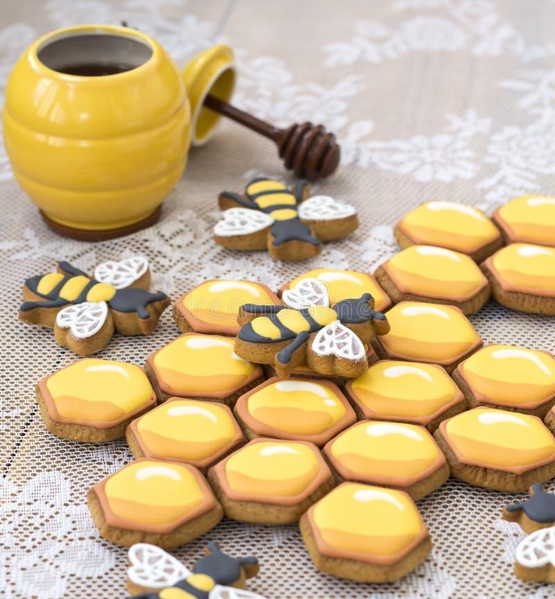 Печенья и пчелы сота на деревянном столе стоковые изображения