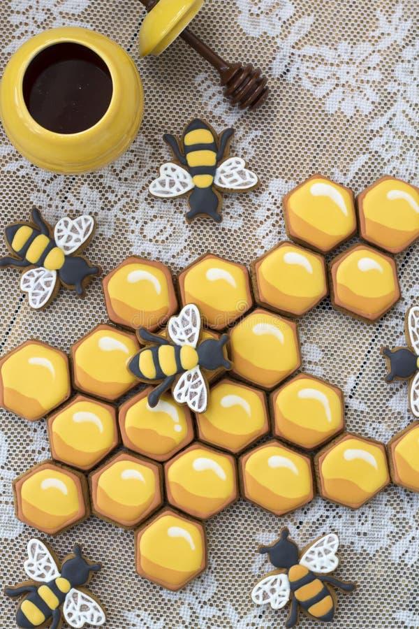 Печенья и пчелы сота на деревянном столе стоковые фото