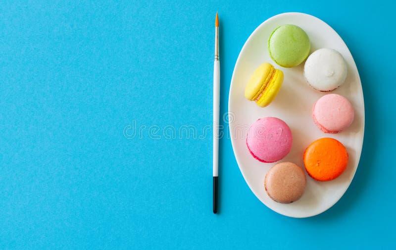 Печенья красочного macarons- французские в белой плите на голубом bac стоковое фото rf