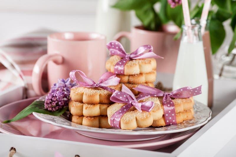 Печенья на белом подносе с кружками, milkshakes и цветками сирени стоковые фото