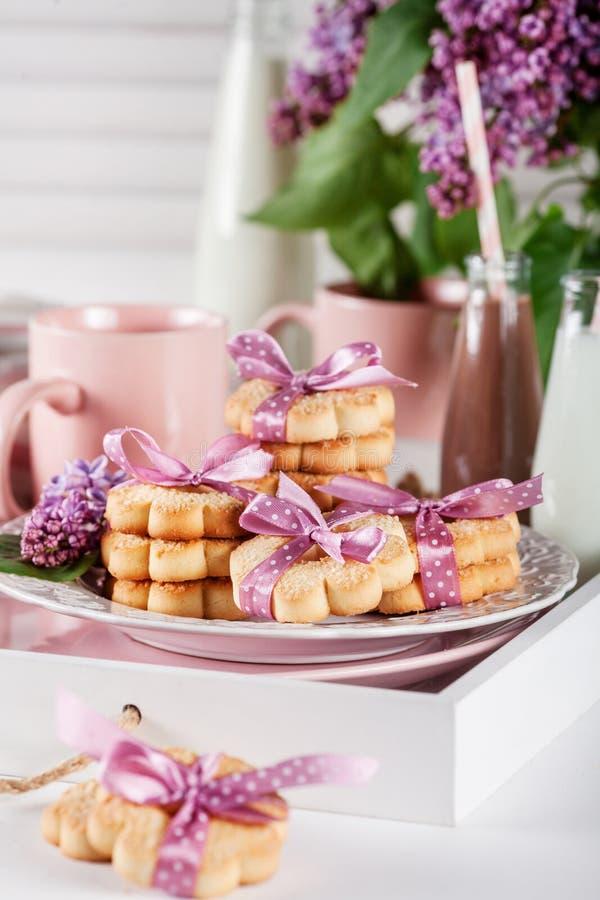 Печенья на белом подносе с кружками, milkshakes шоколада и lila стоковая фотография