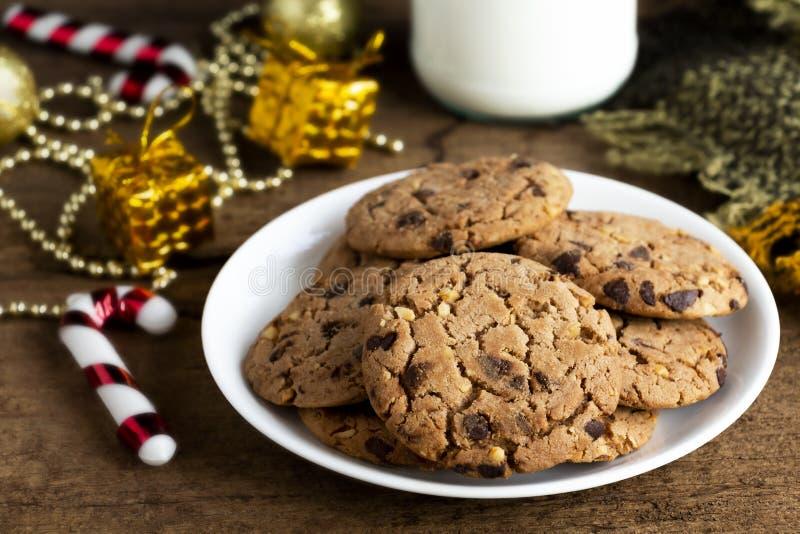 Печенья обломока шоколада свежо испеченные на белой плите со стеклянным b стоковое фото
