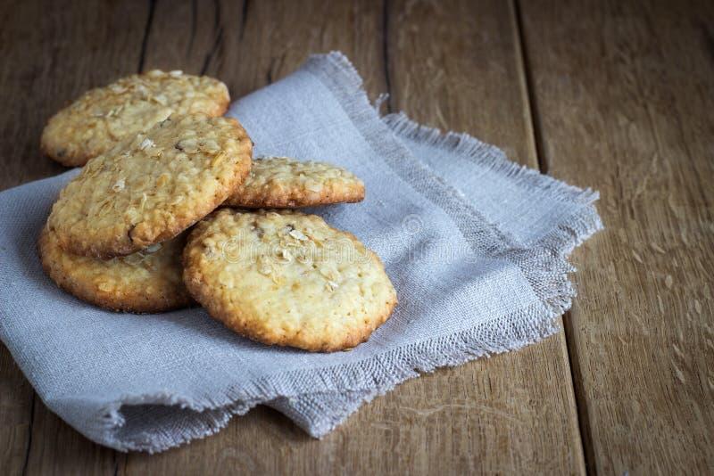 Печенья овсяной каши на белой linen салфетке на деревянном стоковое фото rf