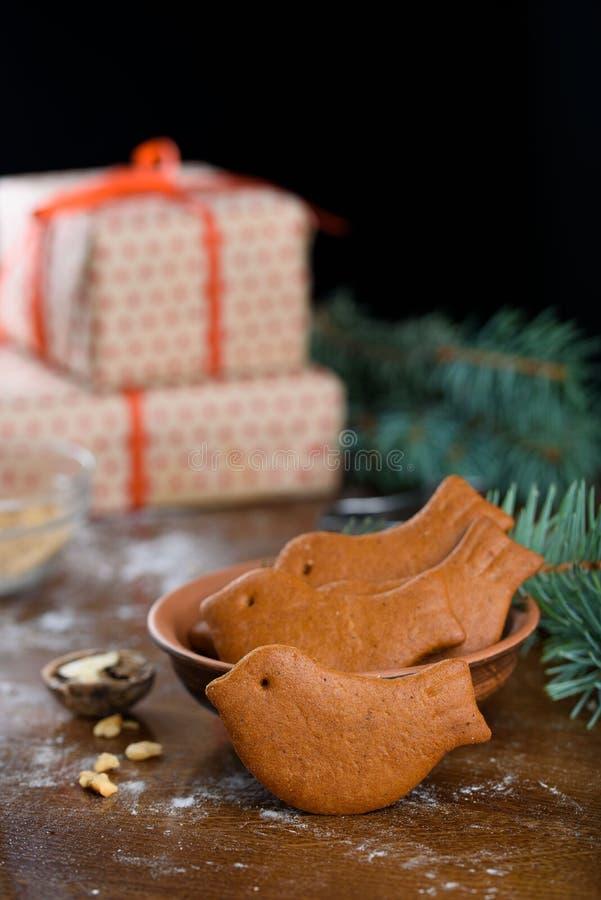 Печенья пряника рождества в форме птицы на таблице Подарки, sprigs спруса, грецкие орехи стоковая фотография rf