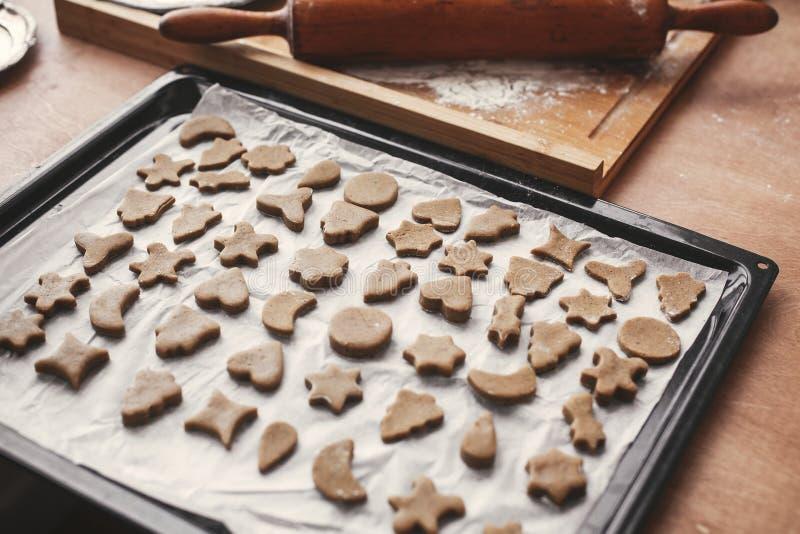 Печенья пряника рождества сырцовые на печь подносе и деревянном крене стоковая фотография