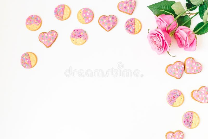 Печенья пряника с розовой поливой и розы на белой предпосылке Плоское положение Взгляд сверху стоковые изображения