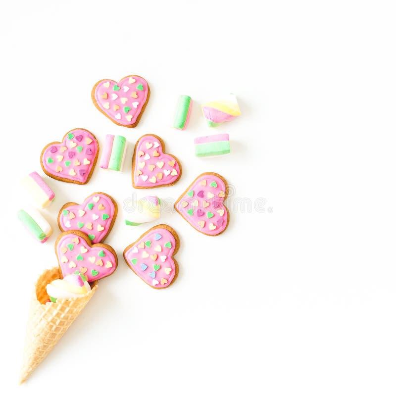 Печенья пряника с розовыми поливой и зефиром в конусе waffle дальше с предпосылкой сердце подарка дня принципиальной схемы голубо стоковые фото