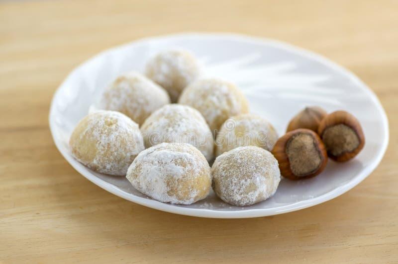 Печенья рождества, вкусные шарики с фундуком внутри и сахаром замороженности, белая плита и деревянный стол стоковое изображение rf