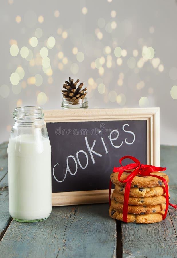 Печенья рождества с молоком в бутылке на ` печений ` деревянного стола и текста на доске мела в деревянной рамке стоковые фото