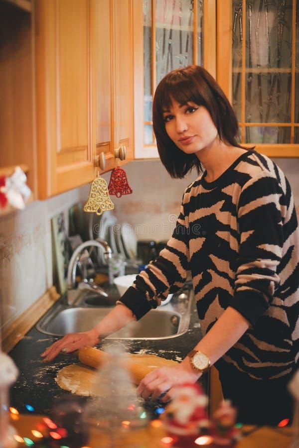 Печенья рождества выпечки молодой женщины на украшенной кухне стоковые фото