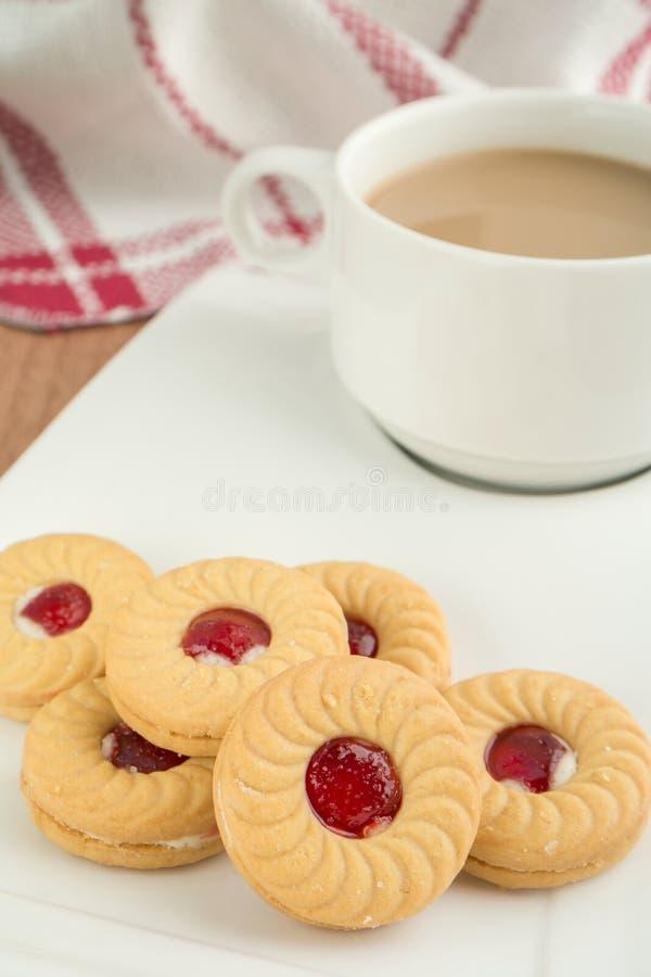 Печенья сандвича варенья клубники с кофейной чашкой стоковое изображение rf