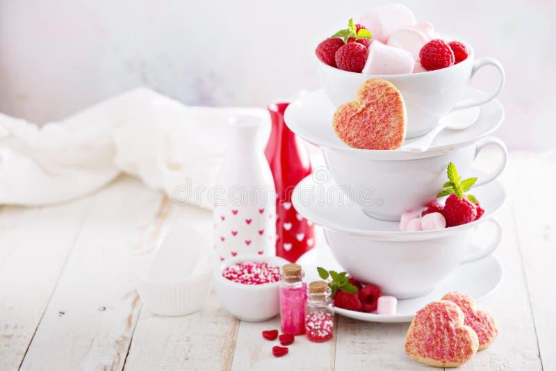 Печенья сахара дня валентинок в штабелированных чашках стоковая фотография