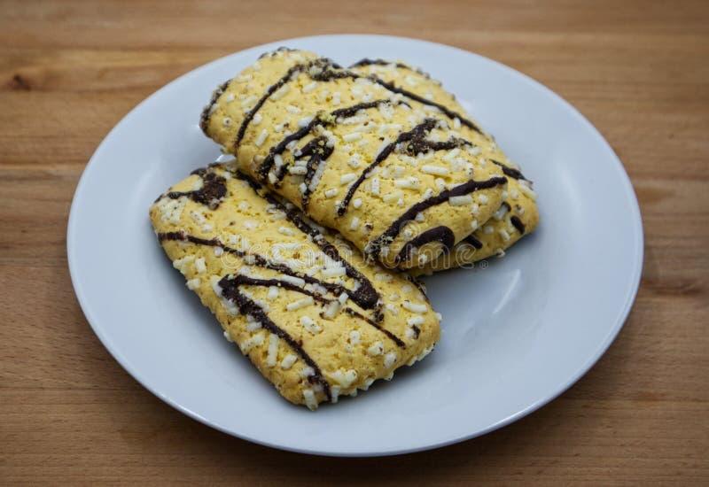 Печенья с кристаллами поливы и сахара шоколада на белом блюде, деревянном столе стоковые изображения rf
