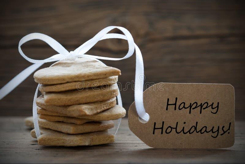 Печенья хлеба имбиря с ярлыком с счастливыми праздниками стоковые изображения