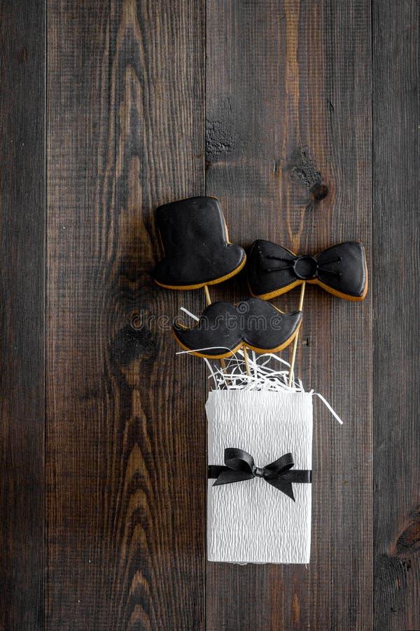 Печенья черного галстука, усика и шляпы на ручках на счастливый день ` s отца представляют печеньям деревянный космос взгляд свер стоковые изображения rf