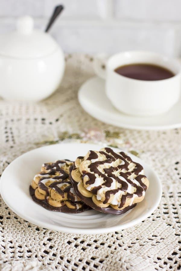 Печенья шоколада на белых плите и чашке чаю на таблице стоковое фото