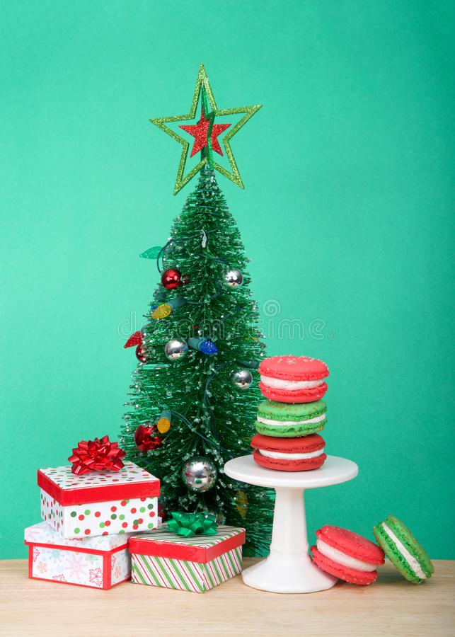 Печенья macaron рождества на небольшом постаменте с рождественской елкой и настоящими моментами стоковое фото