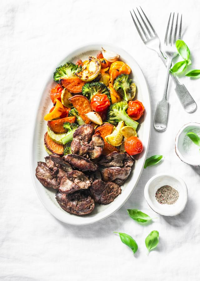 Печень жареной курицы и испеченные сезонные овощи - очень вкусный здоровый обед на светлой предпосылке стоковое фото