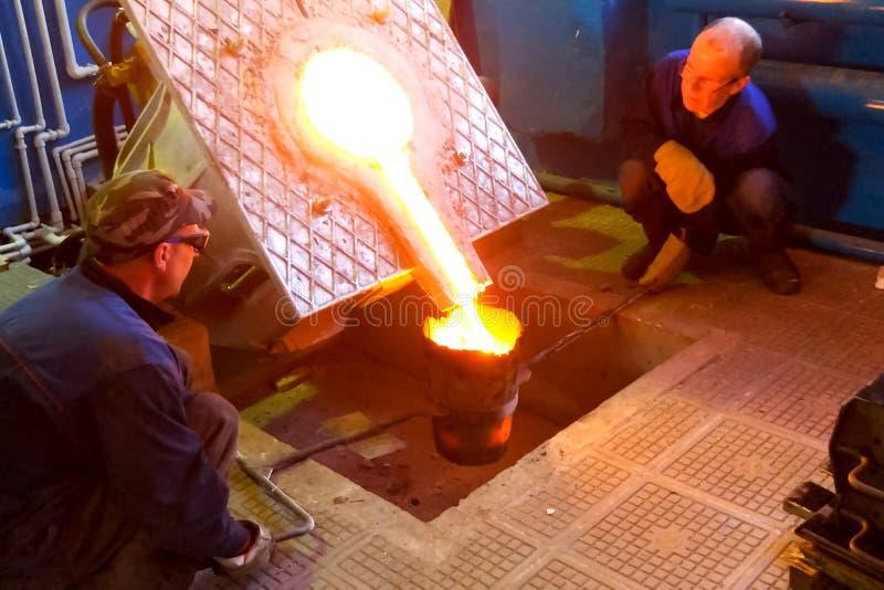 Печь для переплавлять металла Лить металл от печи работниками стоковые изображения