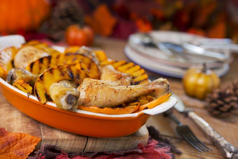 Печь зажарила в духовке цыпленк цыпленок с зажаренной тыквой на деревенской таблице стоковое фото rf