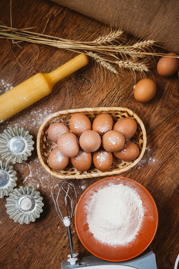 Печь торт в сельской кухне - яичках ингридиентов рецепта теста, муке, сахаре на винтажном деревянном столе сверху стоковая фотография