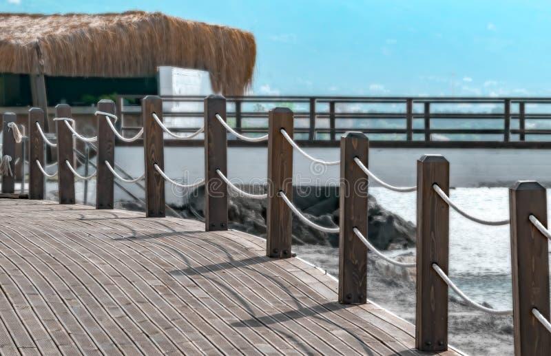 Пешеходный мост по побережью с загородка с веревочкой Предпосылка ландшафта лета моря стоковые изображения rf