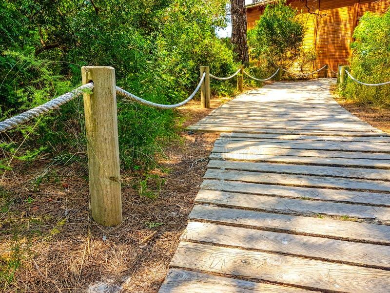 Пешеходный путь сделанный с деревянными планками на столбах пола и поручня и веревочка который достигают деревянный дом стоковые фотографии rf