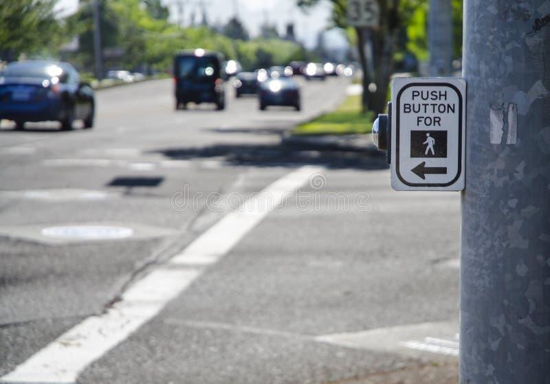 Пешеходные перекрестные знак и кнопка прогулки на оживленной улице с автомобилями a стоковые изображения rf