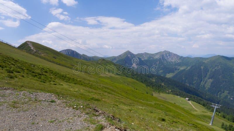 Пеший путь на склоняемых холмах с взглядом на гребнях горы стоковое изображение