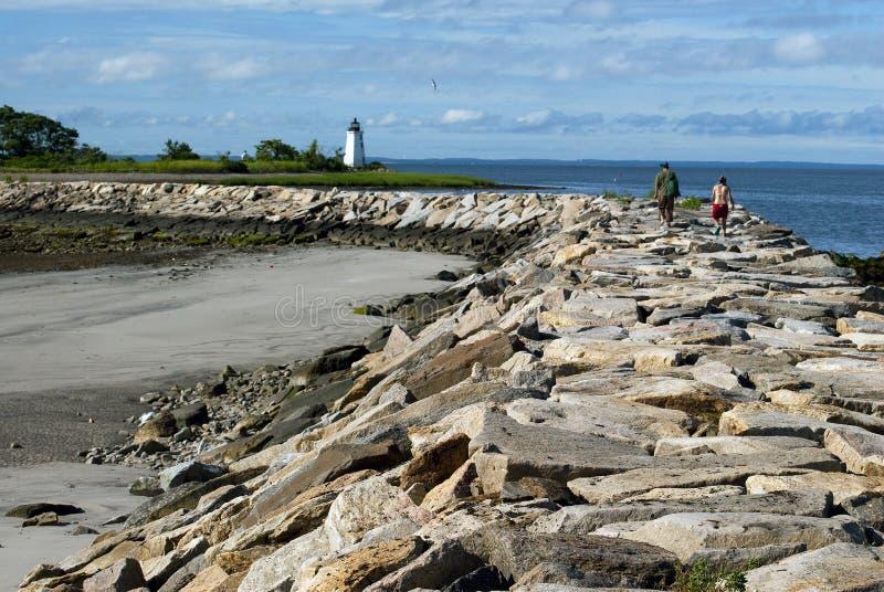 Пеший туризм вдоль волнореза к маяку в расстоянии стоковое изображение