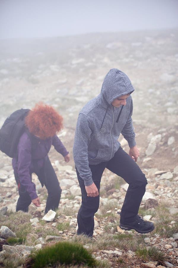 Пеший туризм на горе через туман стоковое фото