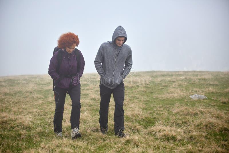Пеший туризм на горе через туман стоковая фотография rf