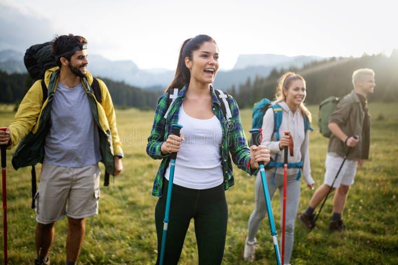 Пеший туризм с друзьями так потеха Группа в составе молодые люди с рюкзаками идя совместно стоковые фотографии rf