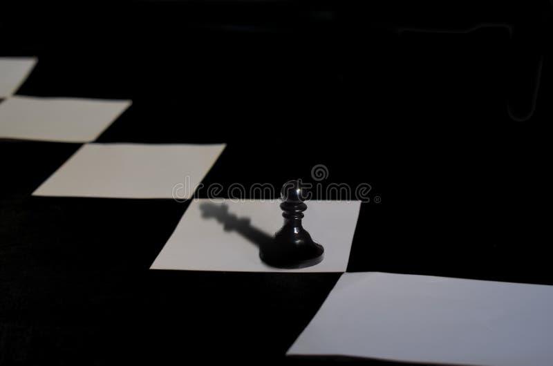 Пешка шахмат с тенью ферзя стоковое фото rf