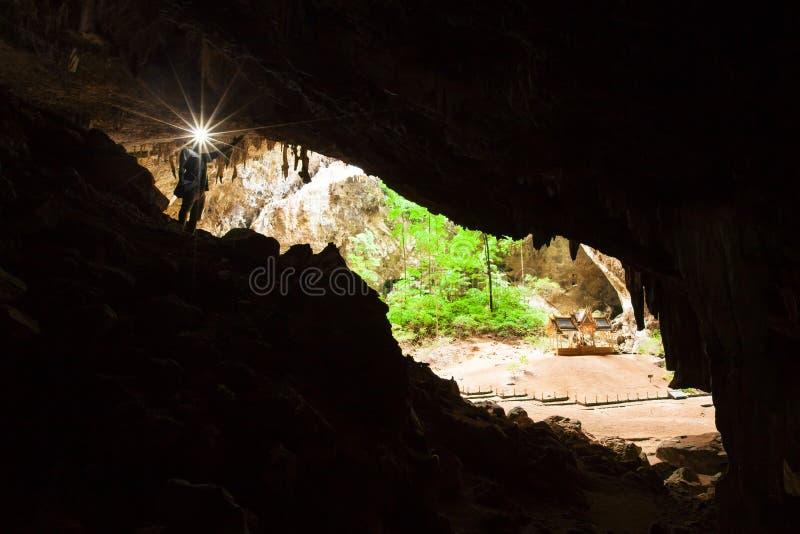 Пещера с факелом, пещера тайны молодого человека исследуя Phraya Nakhon большая пещера которая имеет отверстие в позволять потолк стоковые фотографии rf