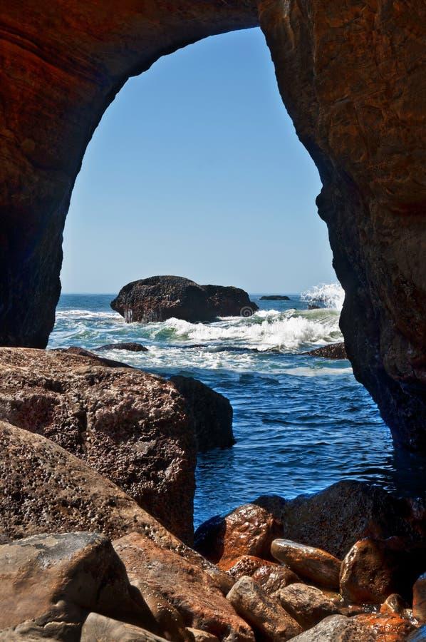 Пещера Punchbowl дьявола смотря вне в волны Тихого океана стоковая фотография