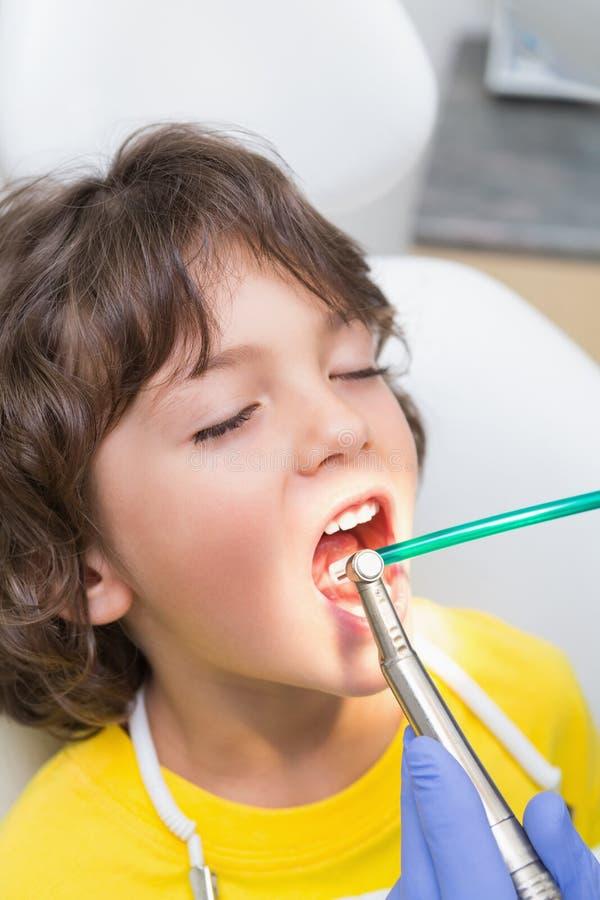 Педиатрический рассматривать дантиста зубы мальчиков в стуле дантистов стоковое изображение