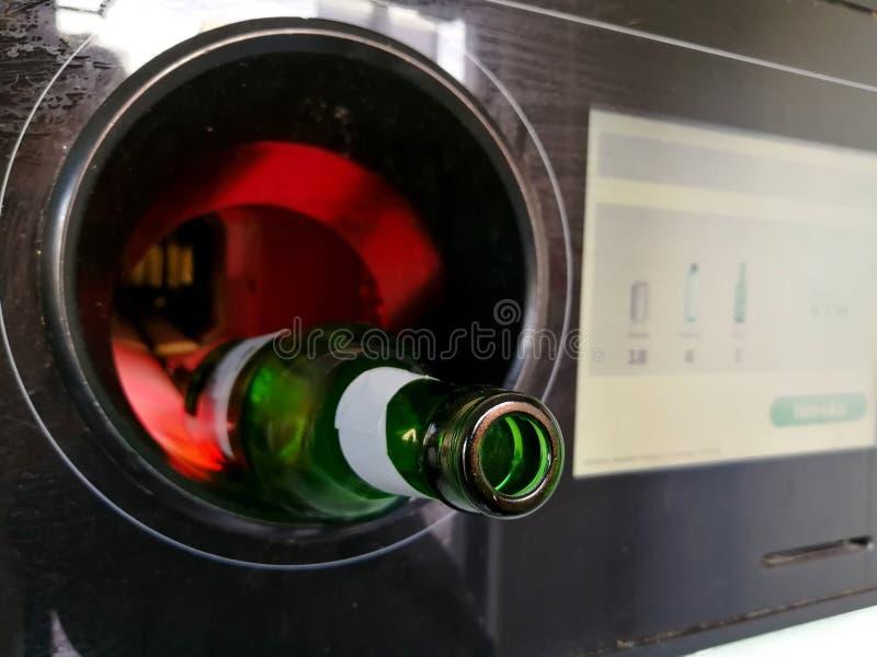 Пивная бутылка введенная в автоматический обратный автомат для повторно использовать стоковое изображение rf