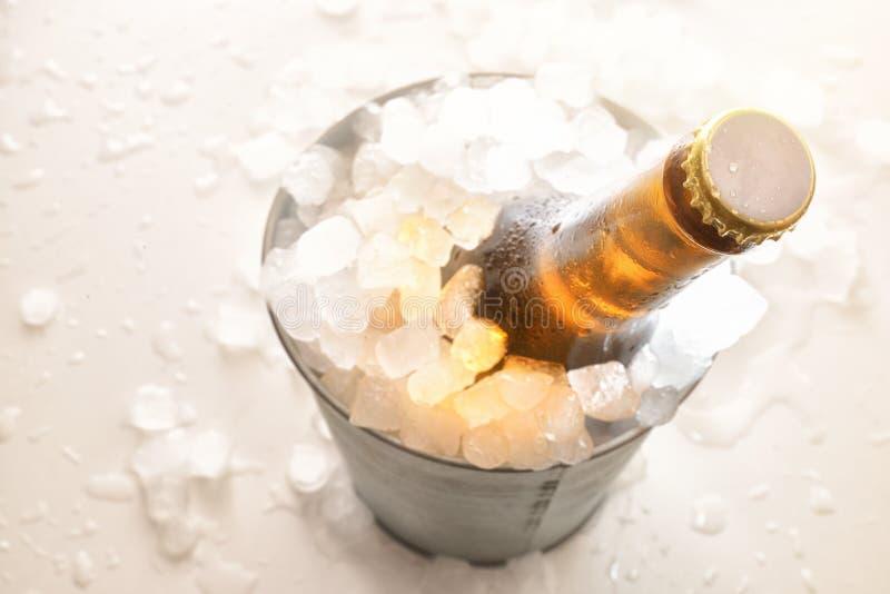 Пивная бутылка в ведре металла вполне кубов льда на белой таблице стоковая фотография rf