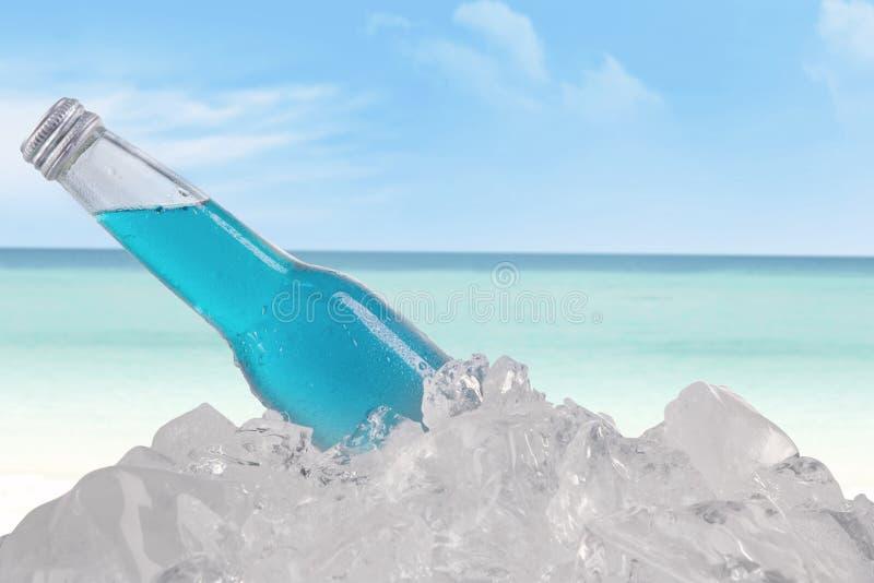 Пивная бутылка на кубе льда на пляже стоковые изображения rf