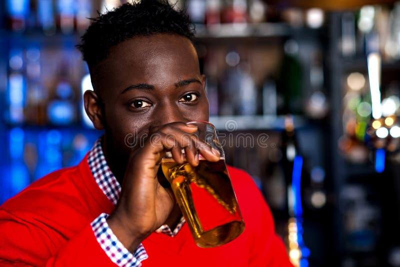 Пиво африканского парня выпивая, предпосылка нерезкости стоковые изображения rf