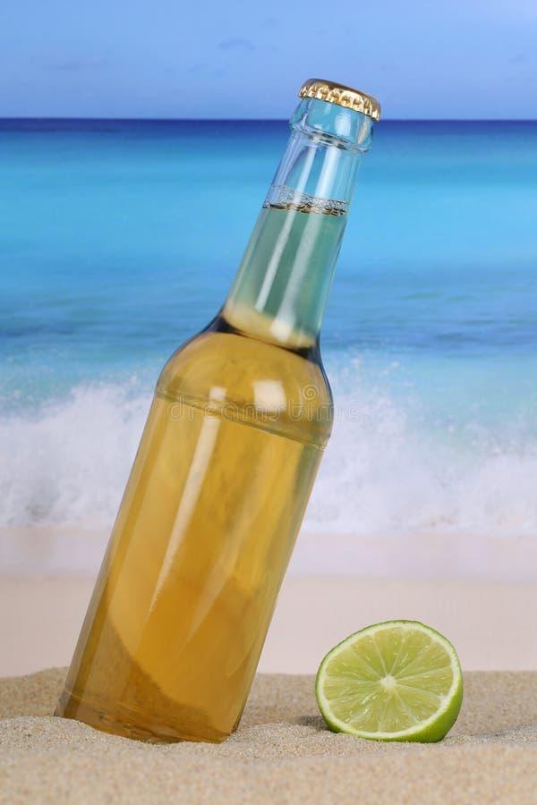 Пиво в бутылке на пляже и песке стоковое фото rf
